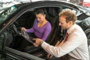Autoverkäufer berät Kundin, die ein neues Auto kaufen möchte, in einem Autohaus
