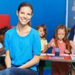 Lächelnde Erzieherin vor Gruppe Kinder beim Malen im Kindergarten