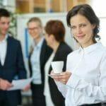 Lächelnde Frau trinkt eine Tasse Kaffee im Büro
