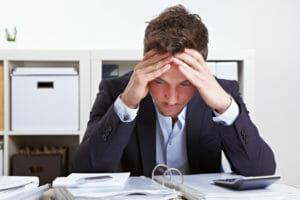 Mann mit Anspannung gebeugt am Schreibtisch