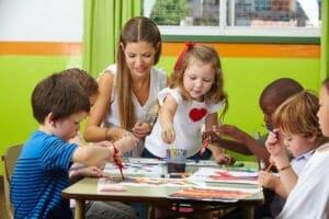 Viele Kinder malen mit Farbe zusammen mit Erzieher im Kindergarten