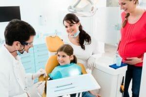 Zahnarzthelferin mit Arzt und Kind